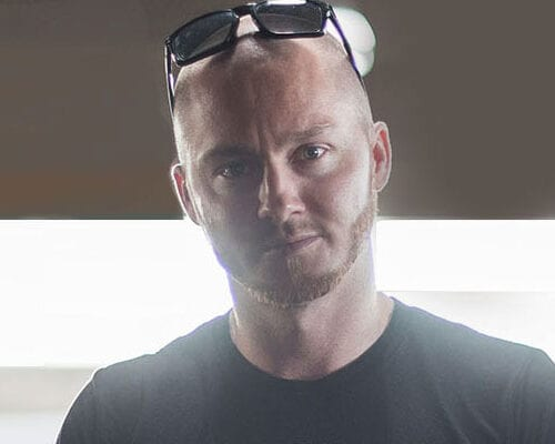 Headshot of a bald white man wearing black sunglasses over his head and a black shirt