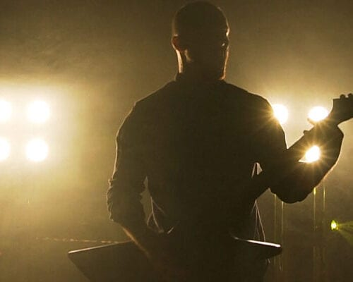 Silhouette of a man holding an electric guitar in front of bright stage lights