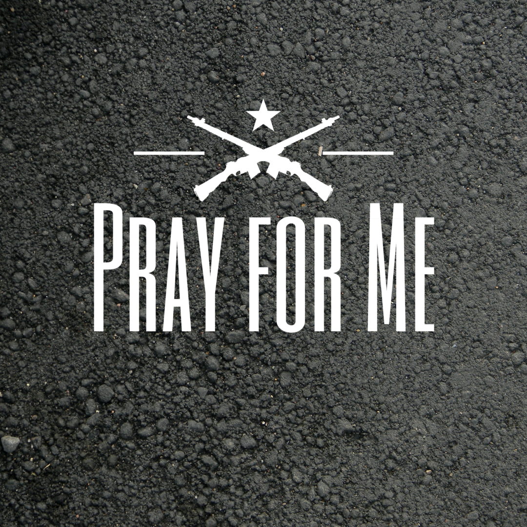 """Rough pavement with the words """"Pray for Me"""" in all caps and a symbol of two riffles crossing below a white star"""