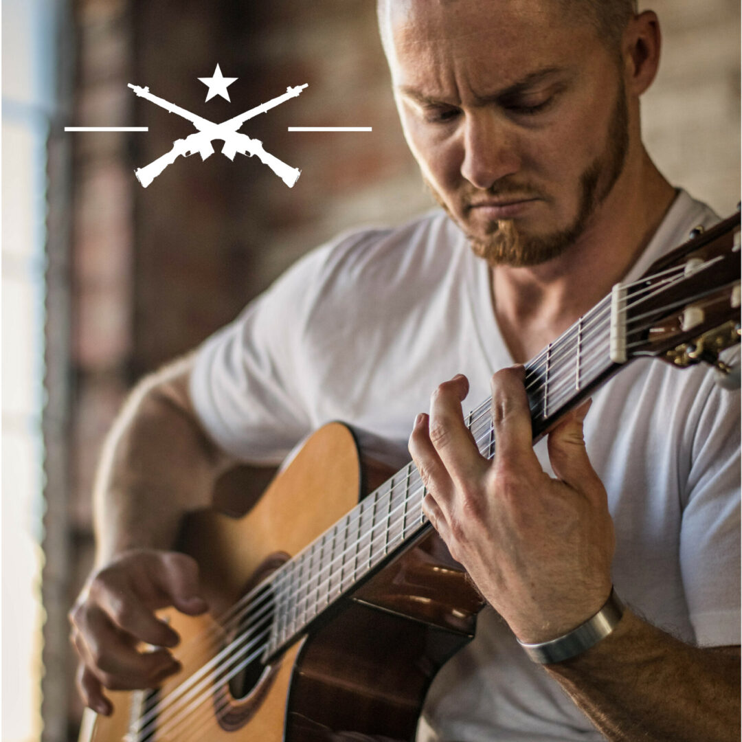 White man in a white shirt holding an acoustic guitar with a symbol of two riffles crossing below a white star