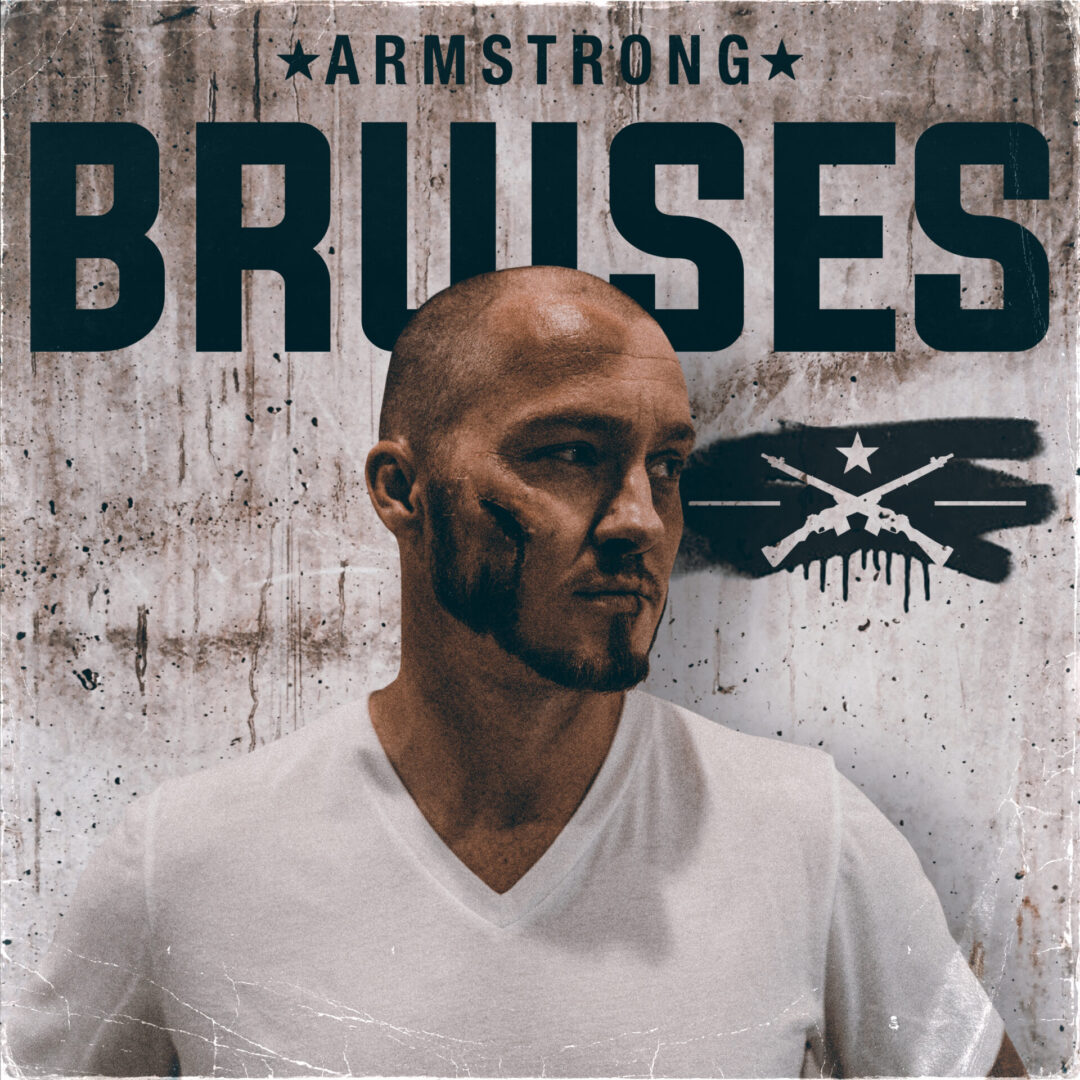 """Man in a white shirt with a bruise on his cheek in front of a wall with """"Armstrong"""" and """"Bruises"""" graffitied on it"""